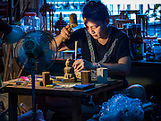 "02 NOVEMBER 2016 - BANGKOK, THAILAND:  GOB, who now runs the family spirit house workshop, works on the small figurines that ""live"" in the spirit houses she makes. She makes the figurines in the living room of her home. There used to be 10 families making traditional spirit houses out of teak wood in Ban Fuen, a community near Wat Suttharam in the Khlong San district of Bangkok. The area has been gentrified and many of the spirit house makers have moved out, their traditional wooden Thai houses replaced by modern apartments. Now there is just one family making the elaborate spirit houses. The spirit houses are made by hand. It takes three days to make a small one and up to three weeks to make a large one. Prices start at about $90 (US) for a small one. The largest, most elaborate ones can cost over $1,000 (US). Almost every home and most commercial buildings in Thailand have a spirit house, which is a shrine to the protective spirit of a the land. Spirit houses are also common in Burma, Cambodia, and Laos.       PHOTO BY JACK KURTZ"