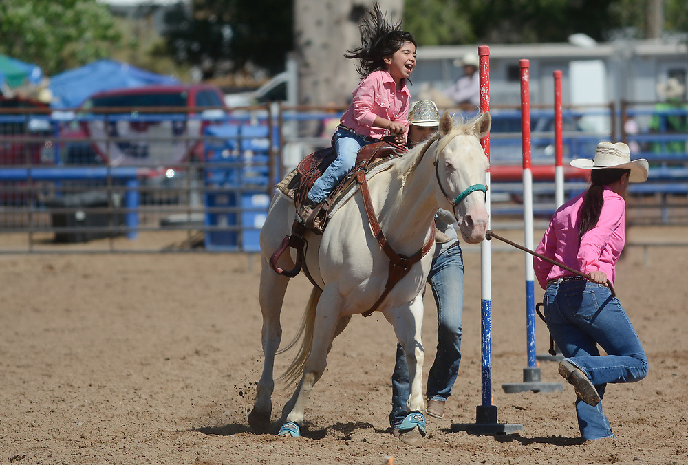 Genesis Aguilar, 6, giggles as she compete in lead line with Tonantzin Candelaria (cq), 15, right, and Mialma Sandoval (cq), behind the horse, Lilly Blanca during the BernCo Bernie Sheep Day and First Impression Youth Rodeo, Saturday, August 5, 2017, at Bernalillo County's Dennison Park Rodeo Grounds in the South Valley. This is the fourth year for the annual event. (Marla Brose/Albuquerque Journal)