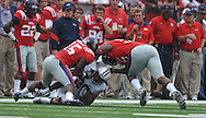 BYU's Chase Pendley (20) is tackled by Ole Miss' Joel Kight (15) and Ole Miss' Cameron Whigham (55) at Vaught-Hemingway Stadium in Oxford, Miss. on Saturday, September 3, 2011. BYU won 14-13.