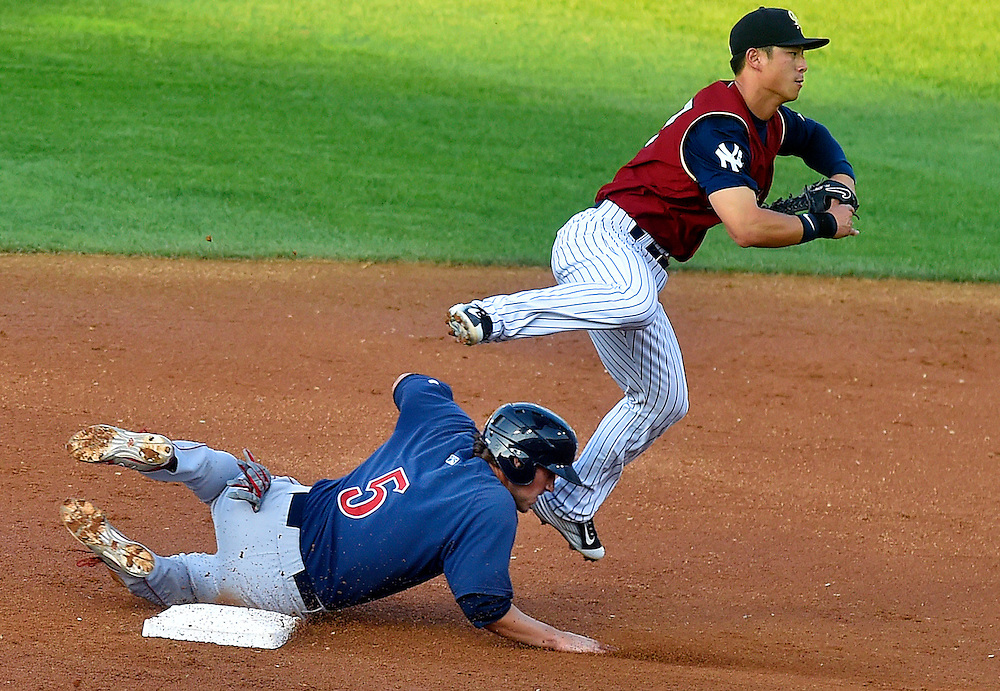 Second Basemen Rob Refsnyder jumps over IronPigs #5 Logan Moore on the turn in the double play.
