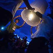 Buddhist monks, western tourist and others gather Saturday, Nov. 16, 2013, near Mae Jo University in Chiang Mai, Thailand to listen to prayers and launch sky lanterns as part of local celebrations of Yi Peng.  The religious ceremony is held to pay homage to Buddha. Yi Peng coincides with  Loi Krathong a religious holiday celebrated throughout Thailand.  (photo by/ David Longstreath)