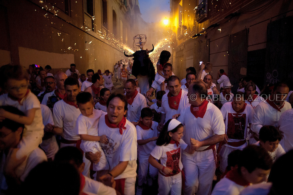 PAMPLONA, SPAIN - JULY 09: A Toro del Fuego (flaming bull) is run through the streets of Pamplona on the fourth day of the San Fermin Running Of The Bulls festival, on July 9, 2013 in Pamplona, Spain. The annual Fiesta de San Fermin, made famous by the 1926 novel of US writer Ernest Hemmingway 'The Sun Also Rises', involves the running of the bulls through the historic heart of Pamplona, this year for nine days from July 6-14.  (© Pablo Blazquez)
