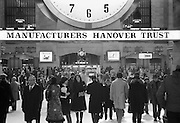 Lunchtime crowd on the concourse of Grand Central Terminal. Backlit by the big clock. Every face tells a story. Every class and type of person including young and old.1975.