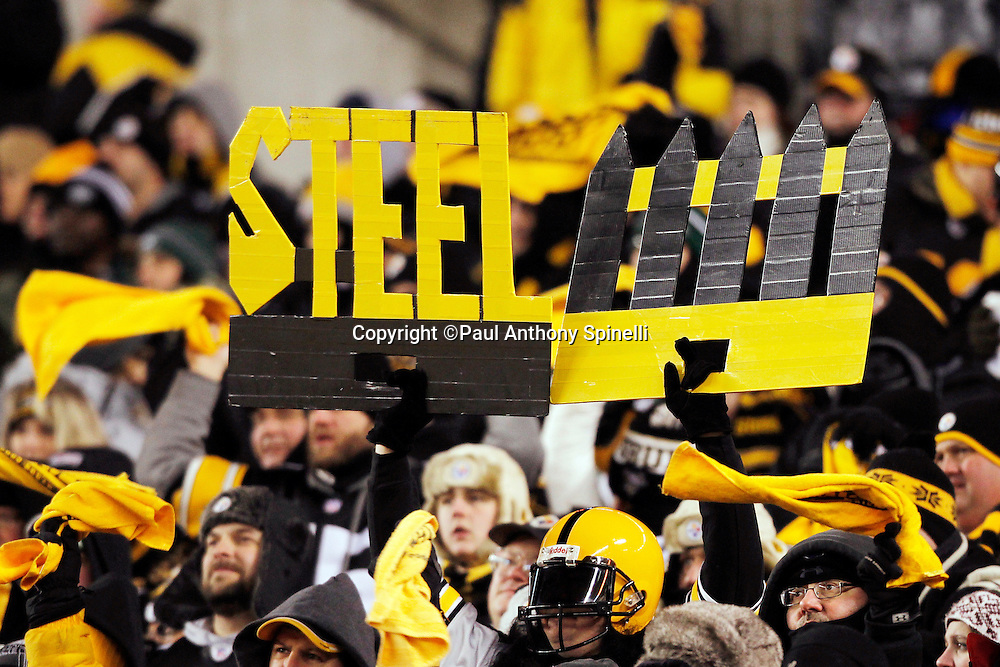 "Pittsburgh Steelers fans wave terrible towels and hold up a ""Steel Fence"" sign during the NFL 2011 AFC Championship playoff football game against the New York Jets on Sunday, January 23, 2011 in Pittsburgh, Pennsylvania. The Steelers won the game 24-19. (©Paul Anthony Spinelli)"