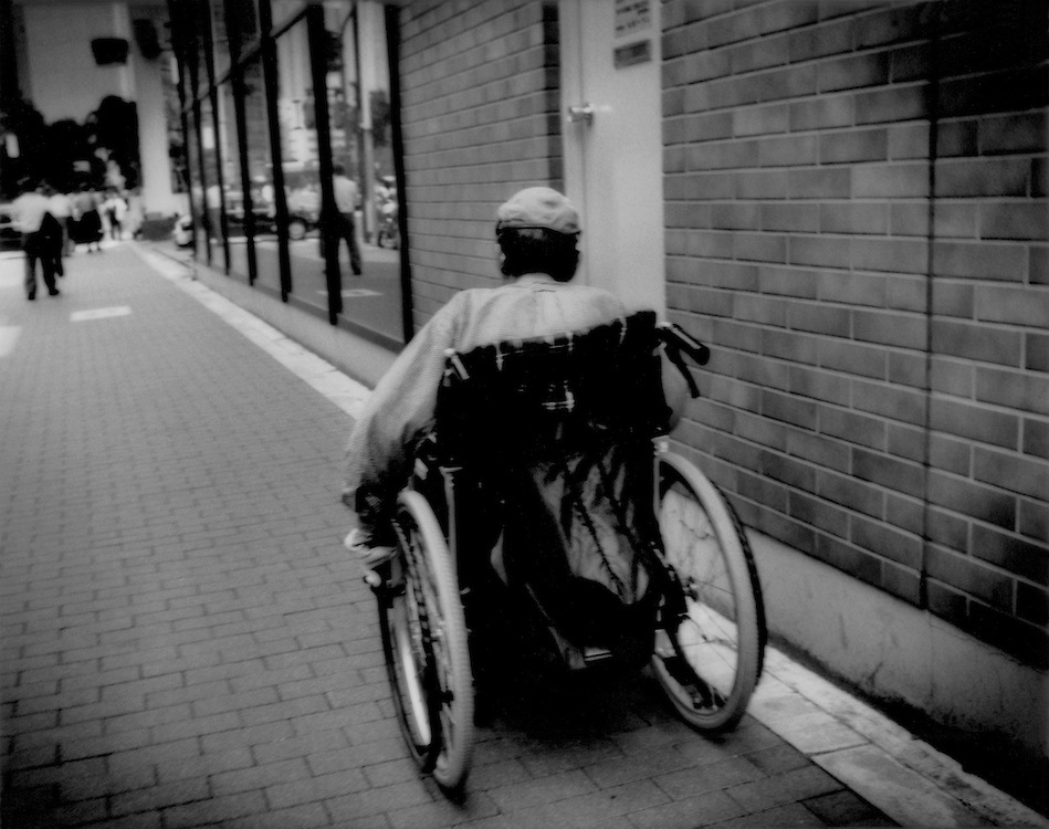 Homeless on streets / Streets like a nursing home:  Homeless man in central Tokyo slowly moves down the street in a wheelchair, Minato-Ku, Tokyo, Japan.