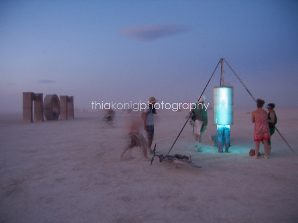 Burners play with an interactive art installation before dawn on the Playa at Burning Man.