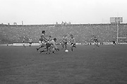Dublin crouches to grab the ball as Kerry comes in from the side during the All Ireland Senior Gaelic Football Final, Kerry v Dublin in Croke Park on the 28th September 1975. Kerry 2-12 Dublin 0-11.