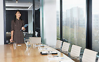 Business woman standing behind table in boardroom