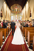 Bride walking down the isle with her father in a church