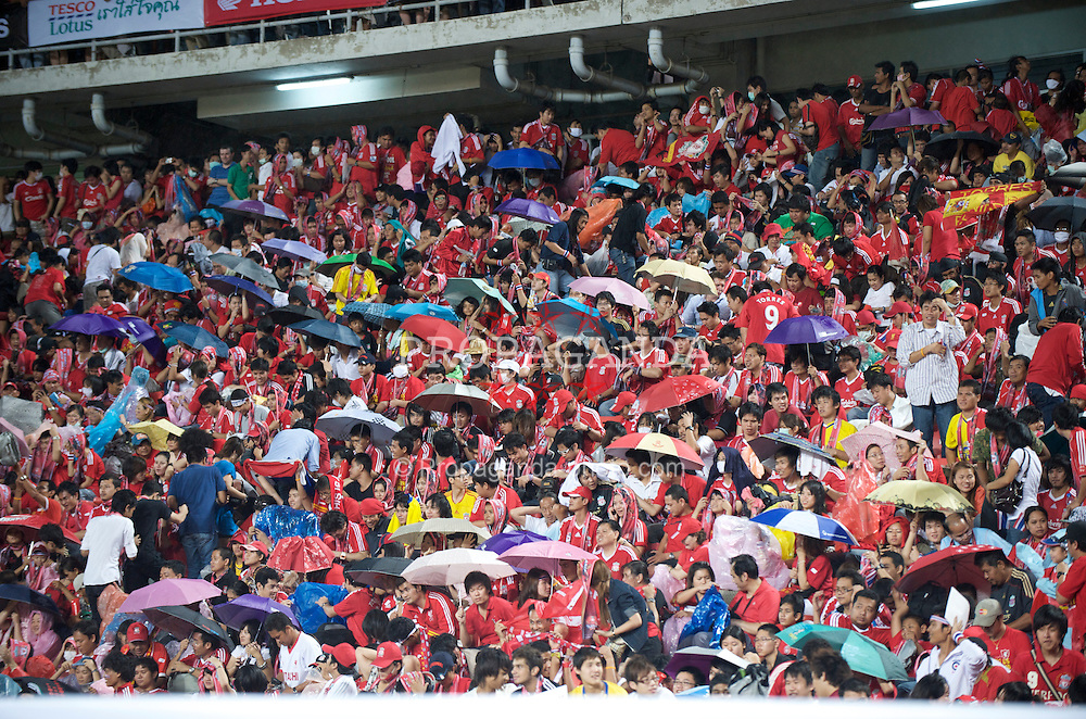 BANGKOK, THAILAND - Wednesday, July 22, 2009: Liverpool supporters shelter under umbrellas as the rain hammers down during a preseason friendly match between Liverpool and Thailand at the Rajamangala Stadium. (Pic by David Rawcliffe/Propaganda)