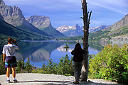 Tourists viewing St. Mary Lake and Wild Goose Island in fall. Glacier National Park, northwest Montana.