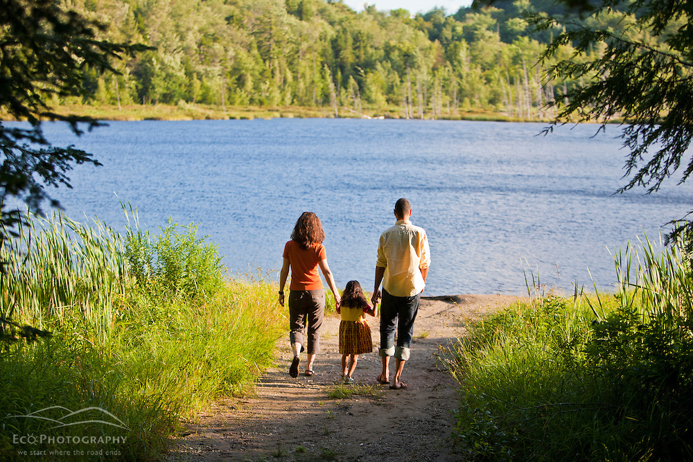 A woman, man, and young girl walk on a path to Mud Pond in Zack Woods, Hyde Park, Vermont. Green River Reservoir State Park
