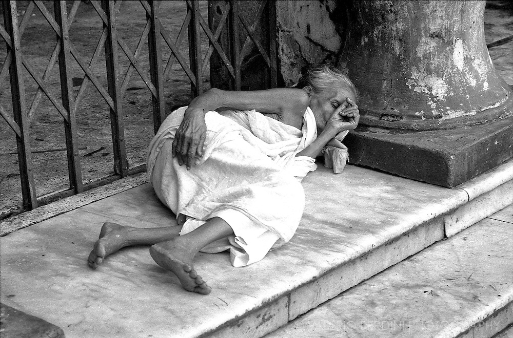 An old woman sleeping on the floor in front of a Hindu temple