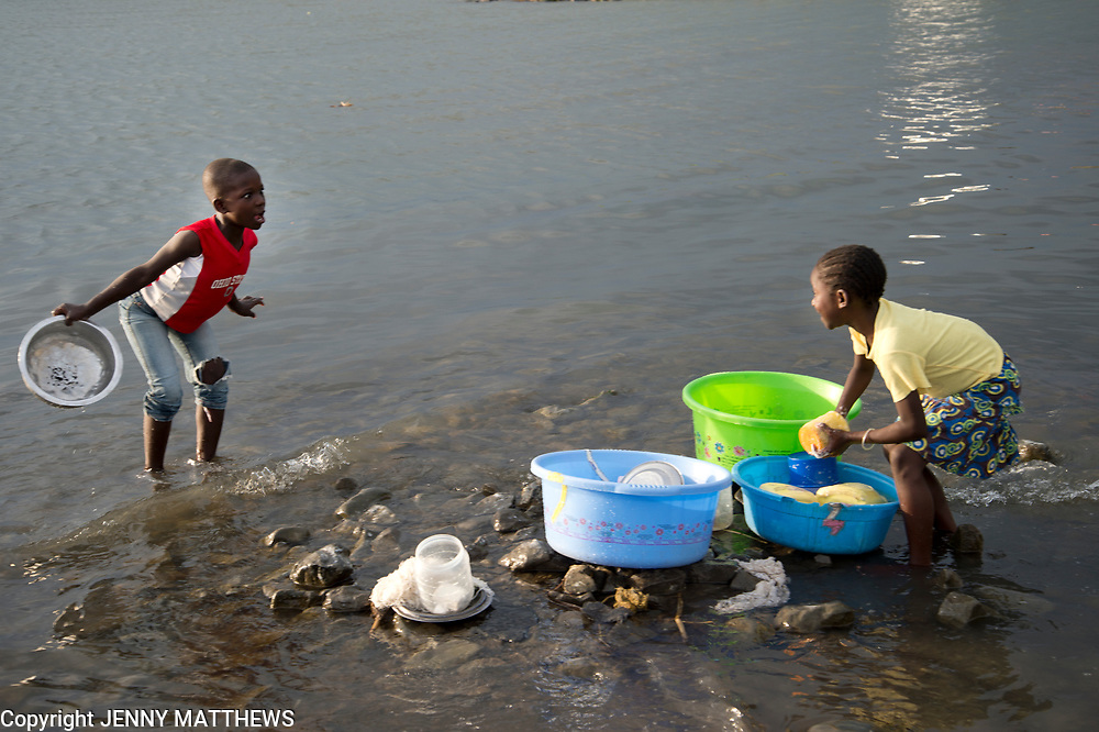 Kenya. Mbita on shore of Lake Victoria. Homa Bay county. Two very young girls washing dishes in the lake.