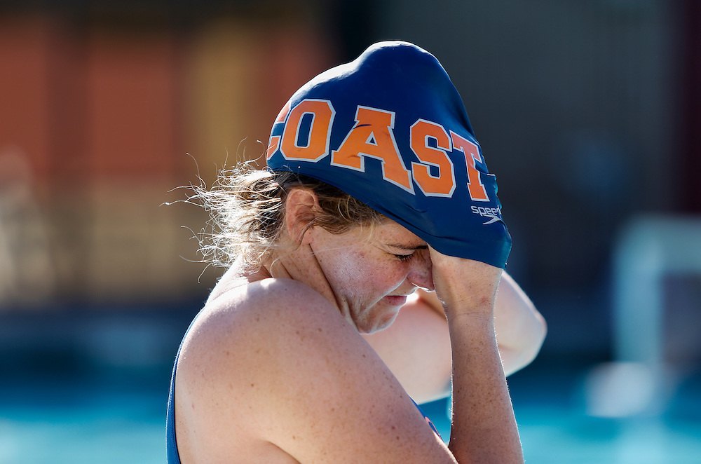On Thursday November 3, during the Orange Empire Conference Women's water polo championship, Alta Cox on Orange Coast College, puts on her swim cap to begin her warm up before the game against Saddleback College in Mission Viejo, CA.  Orange Coast College won the game with the final score of 11 to 4. Photograph taken by ©Mikailin Rae Perry, Sports Shooter Academy