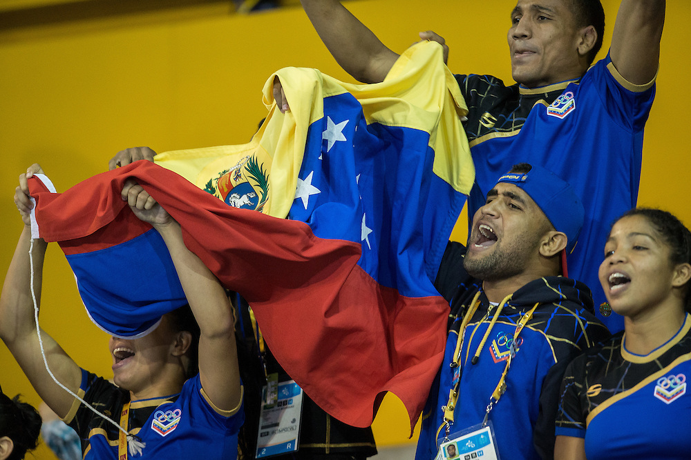 Members of the Venezuelan delegation cheer on a teammate at the men's greco-roman wrestling at the 2015 Pan American Games in Toronto, Canada, July 15,  2015.  AFP PHOTO/GEOFF ROBINS