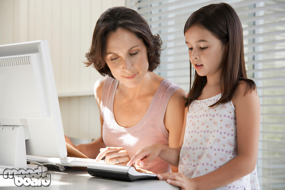Daughter helping mother use computer at home