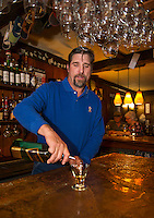 "Ray Simanson pours a glass of scotch in his bar at Tavern 27 to promotes the ""Exquisite Scotch Flight"" an upcoming event later this month.  (Karen Bobotas/for the Laconia Daily Sun)"