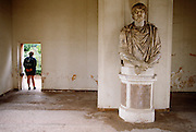 Tourist stands in doorway by unknown bust of Roman figure at Rome's ancient Ceasar's Forum.