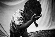 A boy washes his face in a camp for those displaced by the recent earthquake in Petionville, outside Port-au-Prince, Haiti.