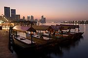 Dubai Creek. Dawn over Deira skyline, Abra (water taxi) station.
