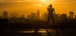 Primrose Hill, London, October 28th 2016. An early morning jogger on Primrose Hill takes a picture of the magnificent sunrise over London's skyscrapers.
