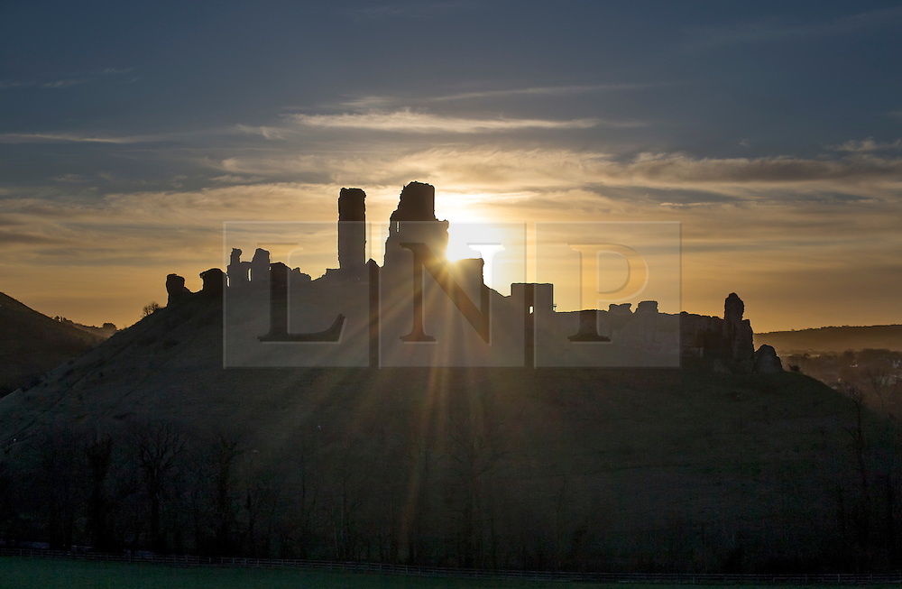 © Licensed to London News Pictures. 28/01/2016. Corfe, UK. The sun rises behind Corfe Castle in Dorset. Parts of the UK are enjoying sunshine today after recent storms. Photo credit: Peter Macdiarmid/LNP