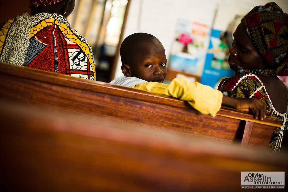 A boy sits in the waiting room of the NDA health center in Dimbokro, Cote d'Ivoire on Friday June 19, 2009.