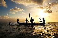 Boys in a canoe at sunset. Rah Lava Island, Torba Province, Vanuatu