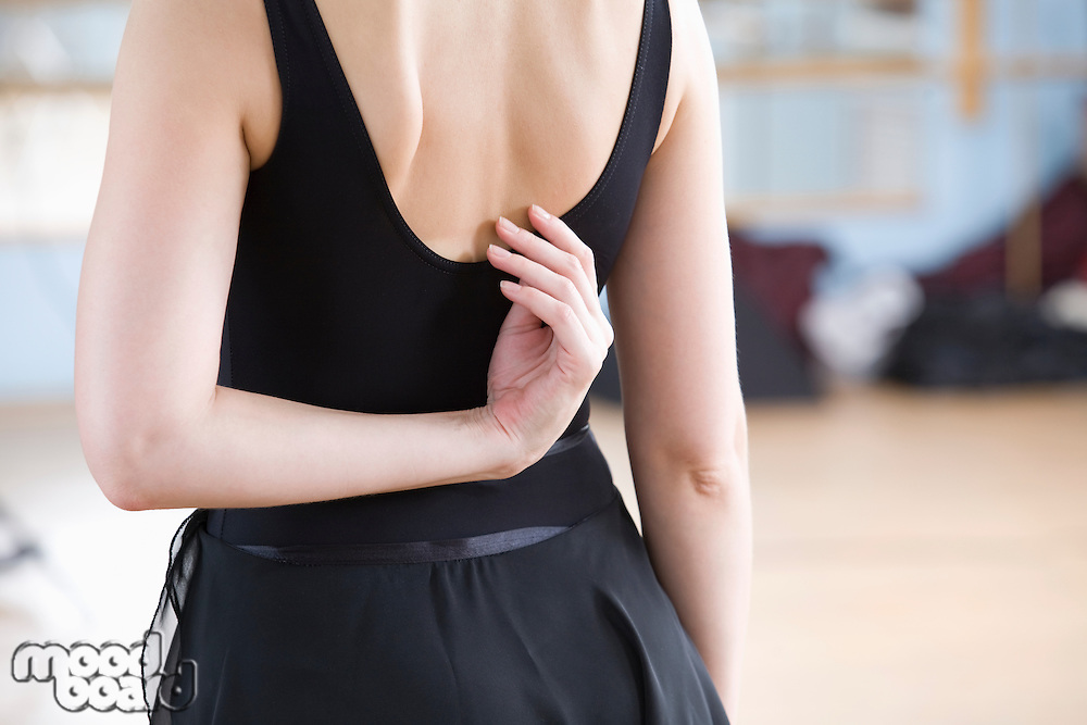 Young woman stretches in ballet rehearsal