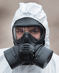 © Licensed to London News Pictures. 23/03/2018. Salisbury, UK. A member of the emergency services in a protective suit and gas mask helps to remove the bench where former Russian spy Sergei Skripal and his daughter Yulia were poisoned with nerve agent in Salisbury. The couple where found unconscious the bench in Salisbury shopping centre on 4th March 2018. Photo credit: Peter Macdiarmid/LNP