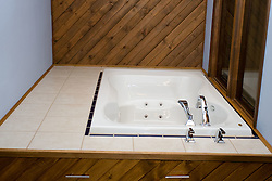 18 June 2011: Jacuzzi whirlpool bath in master suite surrounded by a dual window, diagonal pine car-siding, and porcelain tile deck.  Faucet trim by Delta.