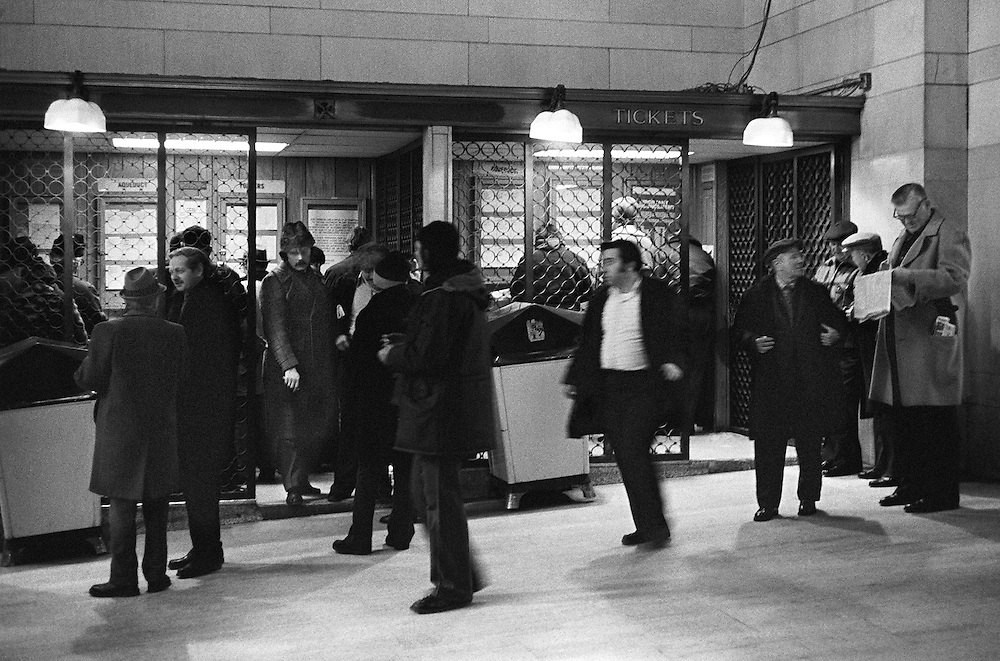 "Ticket Window at Grand Central Terminal. Two groups in conversation, and one line for tickets. Very interesting individual left of center wearing a ""Russion-style"" winter hat. Another person is moving from right to left. The extremely tall and big man to the right catches the eye. A unique assemblage of diverse individuals. 1975."