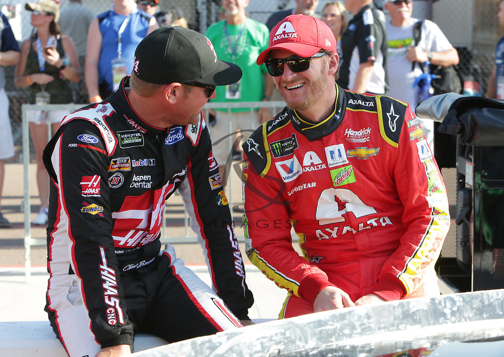 Clint Bowyer and Dale Earnhardt Jr. before qualifying for Sunday's NASCAR Cup Series auto race on Friday, March 17, 2017, in Avondale, Ariz.  (AP Photo/Rick Scuteri)