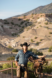 good looking All American Cowboy on a ranch at sunset