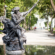 A statue of Neptune slaying a sea monster in Alameda Central, a park in central Mexico City, Mexico.