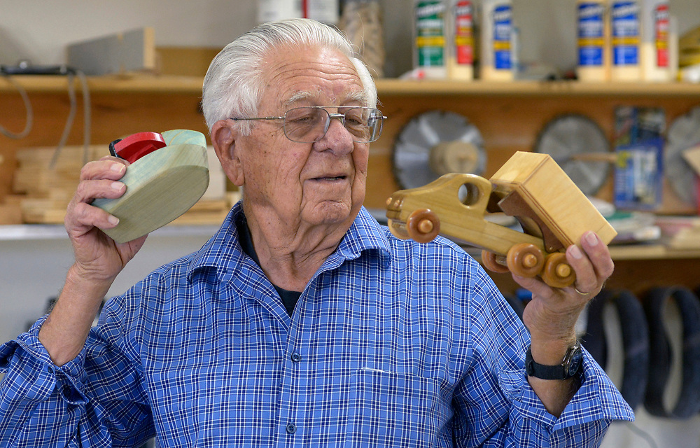 gbs112717e/LIVING --  Jim Templeton, a member of the Albuquerque Woodworkers Association, holds a boat and a dump truck wooden toys members of the association make for charities.(Greg Sorber/Albuquerque Journal)