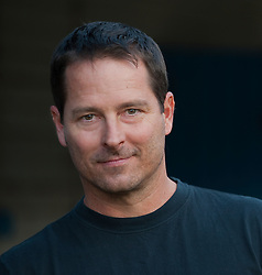 Portrait of a man with a five o'clock shadow in a black t-shirt