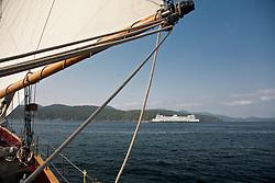 "United States, Washington, San Juan Islands, ferry viewed through sail of schooner ""Adventuress"""