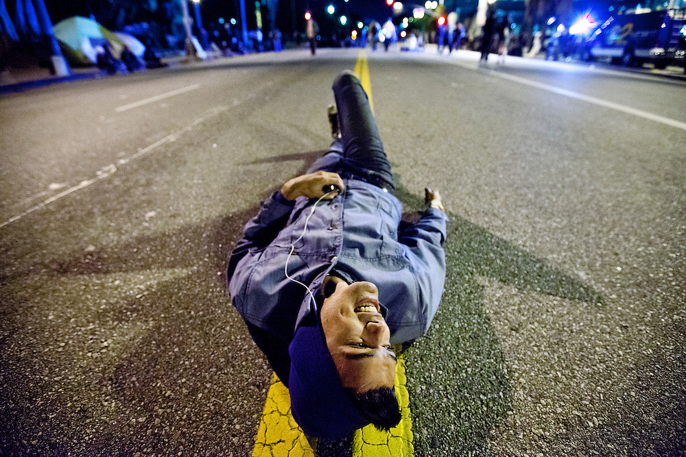 Ty Foster lays in the middle of Spring St. in front of city hall in a show of civil disobedience during Monday mornings demonstrations in Los Angeles, Calif. on November 27, 2011. (Photo by Gabriel Romero ©2011)