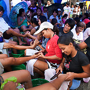Women learn pedicure in a makeshift workshop set up by Laura Vicuña staff. There is very little work in the slums and many women do not have any vocational training so being able to set up a small shop in the streets providing pedicure is a great help to many women.  Because of poverty and lack of income children and young women are easy prey to human traffickers and the foundation aim to teach the dangers of trafficking by showing films in a mobile cinema.Laura Vicuña is a non-profit charity working in Manila and in Bacolod in the state Negros Occidental in the Philippines.