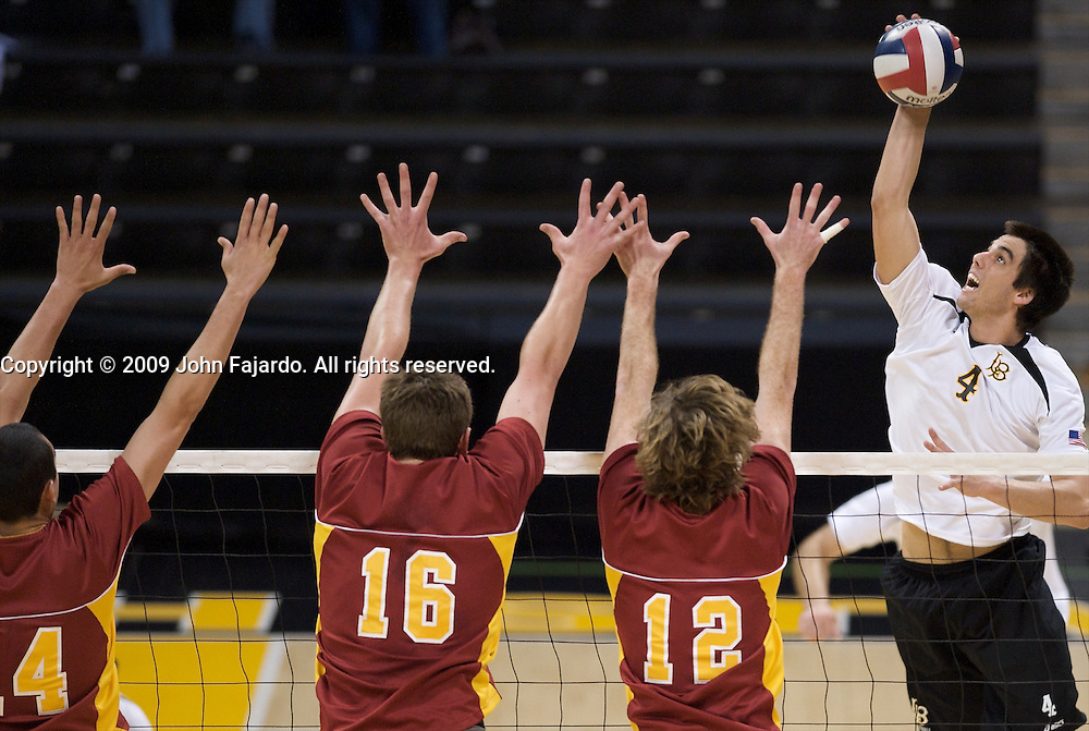 Long Beach State's Tommy Pestolesi(4) attacks the block of Tony Ciarelli(14) Austin Zahn(16) and Sean Dennis(12) in Mountain Pacific Sports Federation play against USC at the Walter Pyramid, Long Beach CA, Wednesday, March 4, 2009.  Long Beach State loses in five sets, 31-29, 24-30, 30-23, 23-30, 13-15.