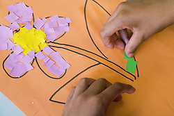 Teenager with learning disability making a picture of a flower in an art class,