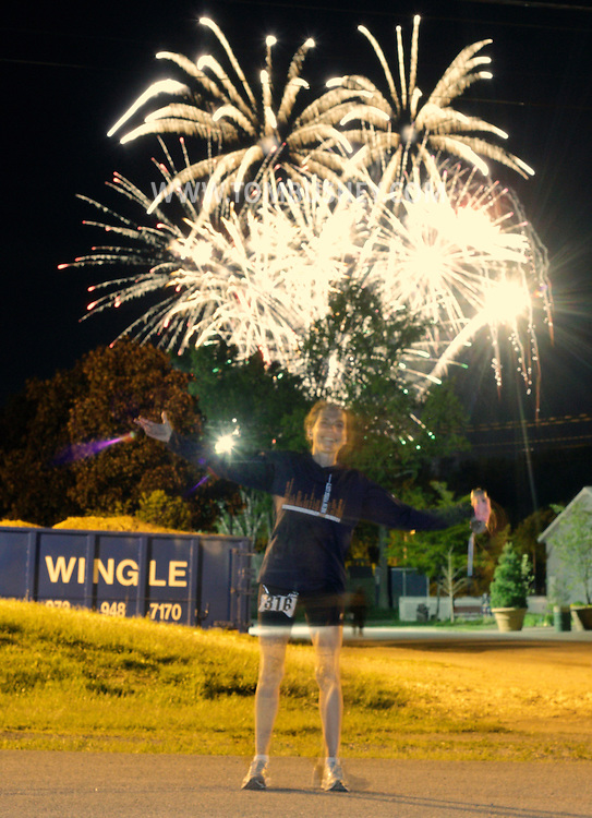 Augusta, New Jersey - Susan Warren stops to have her photograph taken with fireworks going off in the background at Sussex County Fairgrounds during the 3 Days at the Fair races on Saturday, May 15, 2010. Warren was the women's first-place finisher in the 24-hour race.