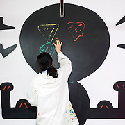 "March 10, 2012 - New York, NY : Misaki Kawai, standing atop a ladder, paints with her fingers as she continues the installation of her new exhibit ""Love from Mt. Pom Pom,"" at the Children's Museum of the Arts in the south village on Saturday March 10. CREDIT: Karsten Moran for The New York Times"