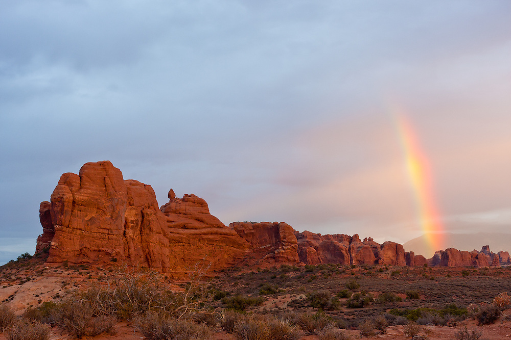 A rainbow shows up in the distance near a rock formation besides Balanced Rock on Arches National Park, Utah.