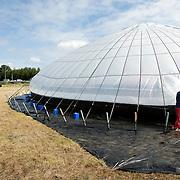 Nederland Delft 30 augustus 2007 20070830..Ingenieur Rudolf Nitzsche, tel 015 2129613 Pino Ciampienetti tel 070 3656368, medewerker organisatie, maken de ingang van de waterpiramide dicht.  ..Waterpiramide op zonne-energie.Langs de A13 bij Delft is vanaf donderdag een piramide te zien die water zuivert op zonne-energie. Het bijna negen meter hoge bouwwerk wordt normaal gesproken in ontwikkelingslanden opgebouwd om zout en vervuild water te destilleren..Ôøº.De bedenker, ingenieur Martijn Nitzsche, demonstreert zijn uitvinding deze maand wegens het lustrum van de TU Delft. ..De waterpiramide is een grote witte tent met een grondoppervlakte van zo'n 650 vierkante meter, die vooral in de tropen, nabij de kust, wordt ingezet. Het zoute water dat in de piramide wordt gepompt, verdampt als overdag de zon op het doek schijnt en de lucht in de tent tot zo'n 75 graden oploopt. Het vuil en het zout blijven op de grond achter en het schone, zoete water druppelt langs de binnenkant van het doek om in een gootje te worden opgevangen. Per dag wordt op deze manier zo'n 1500 liter gegenereerd, dit water kan via jerrycans naar de verschillende dorpen in de omgeving worden gebracht.  ..,,In Afrika staan nu twee van deze tenten. Binnenkort komen er nog vier in Azi?´ bij'', aldus Nitzsche. De Wereldbank beloonde de Delftse ingenieur in 2006 met de innovatieprijs van 190 duizend dollar voor zijn uitvinding. ..Aanvullende info: www.waterpyramid.nl.The need,Ä®.Ôøº.The need for safe, clean drinking water is increasing rapidly. Natural supplies can no longer cope, and shortages happen around the world - especially in tropical and developing counties. There is often enough water available, but it is salty, brackish or dirty, and needs cleaning to make it safe to drink.,Ä®,Ä®Governments, scientists and engineers are working on .Ôøº.ways to do this, but existing methods such as 'multi flash distillation' or 'reverse osmosis' have many drawbacks. The equipment