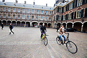 In Den Haag rijden twee fietsers over het Binnenhof.<br /> <br /> In The Hague two cyclists ride at the Binnenhof.