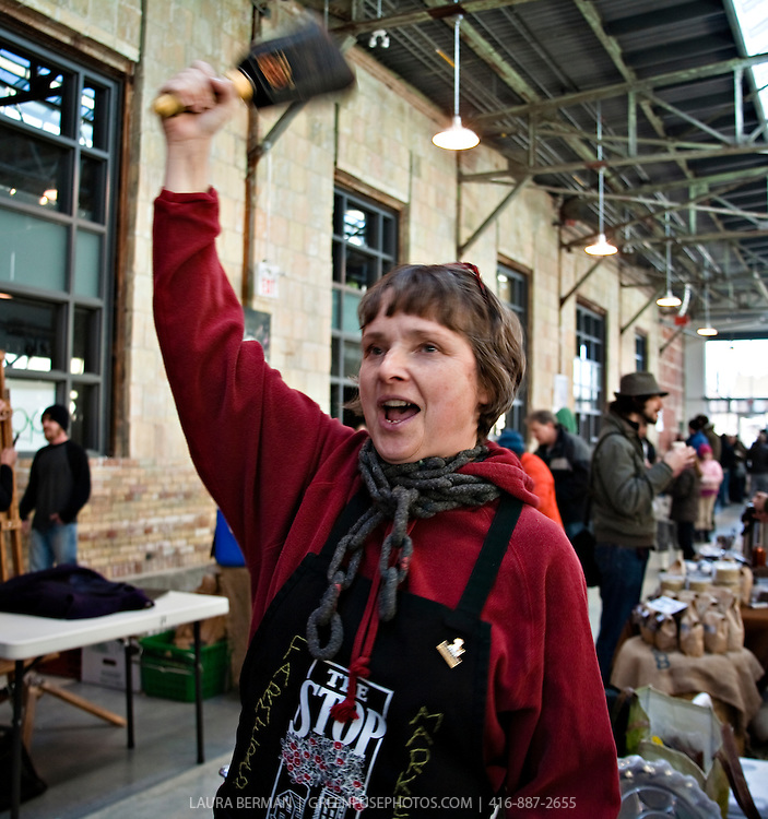 Roscoe Handford manager of the Wychwood Barns farmers' market, rings the bell to signal the end of the market day.