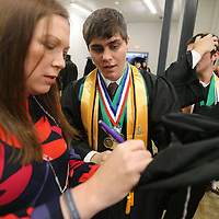 Susan Martin, an English teacher at Mooreville High School and a class sponsor, puts Tyler Estes name in his at as he looks on so he will be able to locat it after tossing it into the air at the end of graduation.